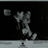 Black and white photograph featuring Donal McCann and Angelica Huston in the back of a carriage on the set of